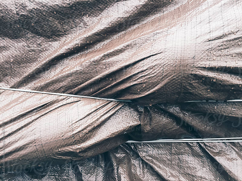 Close up of bound tarp, covering commercial fishing equipment by Paul Edmondson for Stocksy United