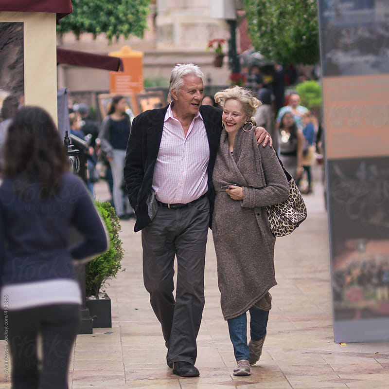 Happy couple in their 60s walking in a city by Per Swantesson for Stocksy United
