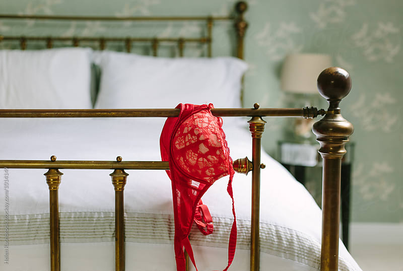 Red lingerie hanging over the end of a metal bedstead by Helen Rushbrook for Stocksy United