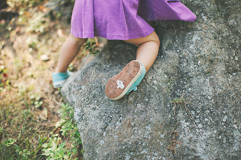 little girl climbing rocks with a sticker stuck to her sneaker by Meaghan Curry for Stocksy United