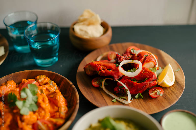 Assorted Indian dishes, focused on tandoori chicken by Alita Ong for Stocksy United