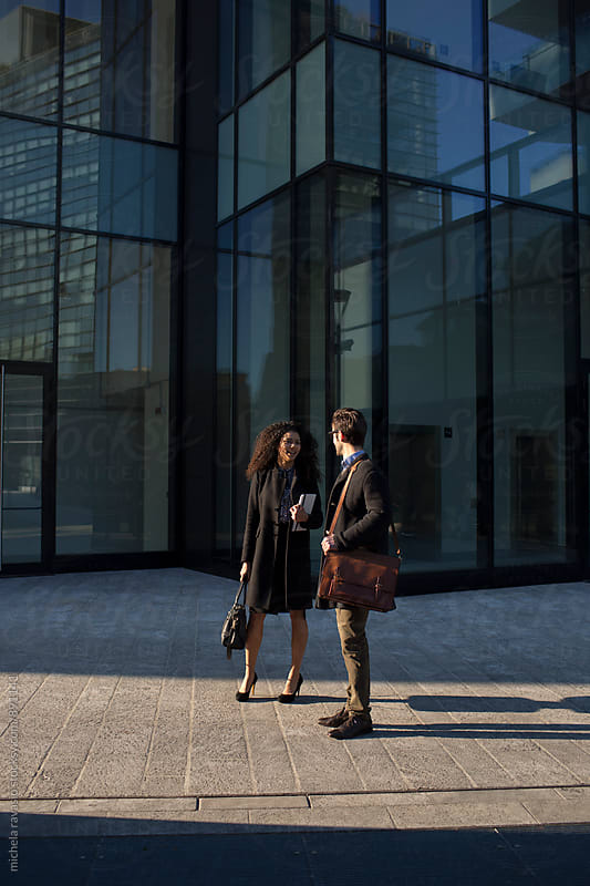 Young business people talking together outside of a corporate building by michela ravasio for Stocksy United
