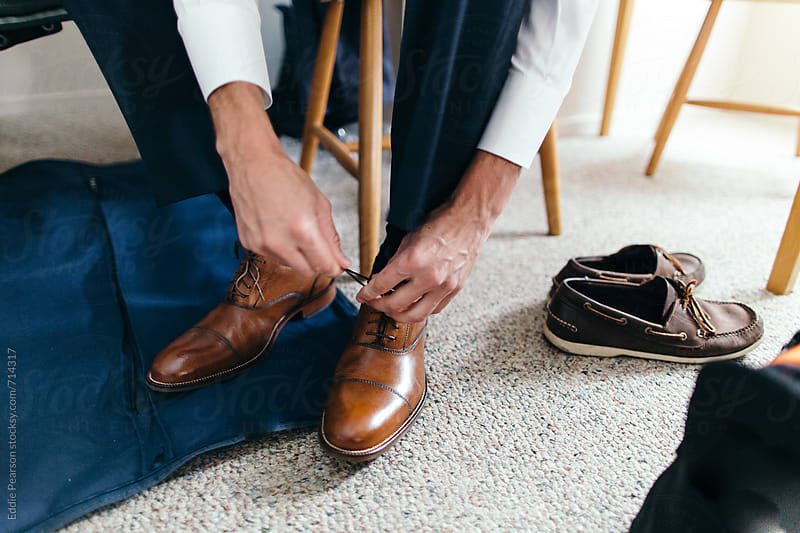 Business man fixing his dress shoes by Eddie Pearson for Stocksy United