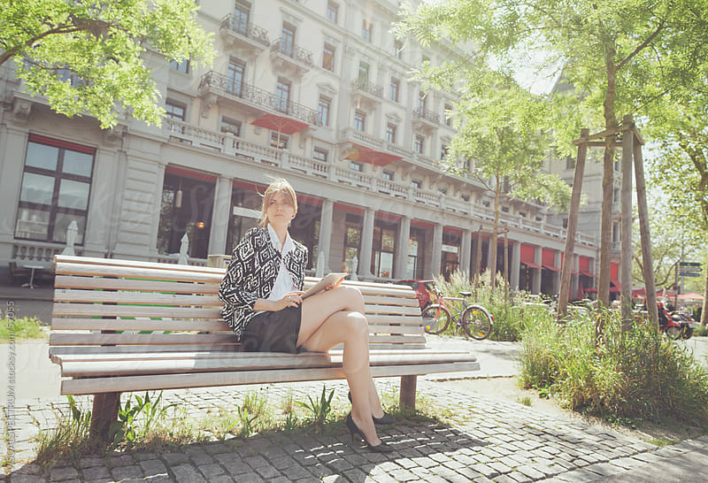 A Woman Holding a Digital Tablet and Sitting on a Park Bench by VISUALSPECTRUM for Stocksy United