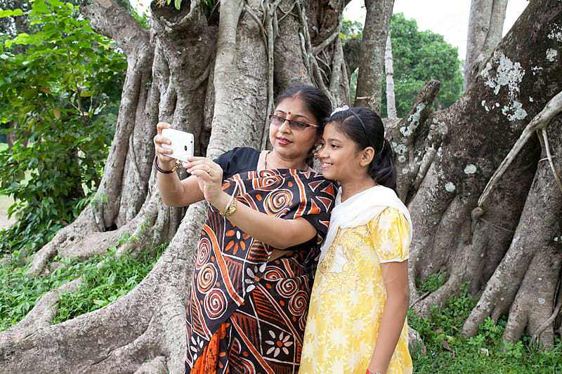 Mother and daughter taking selfie with smartphone by PARTHA PAL for Stocksy United