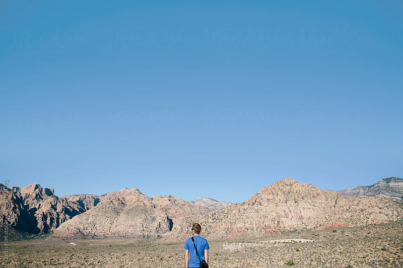 Man standing looking at an amazing view of mountains by Curtis Kim for Stocksy United