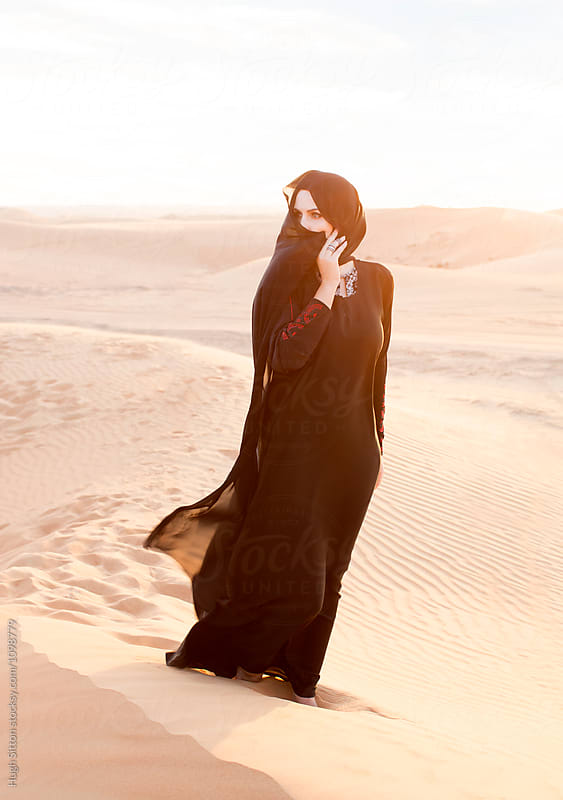 Middle Eastern woman wearing hijab in desert. Dubai. by Hugh Sitton for Stocksy United
