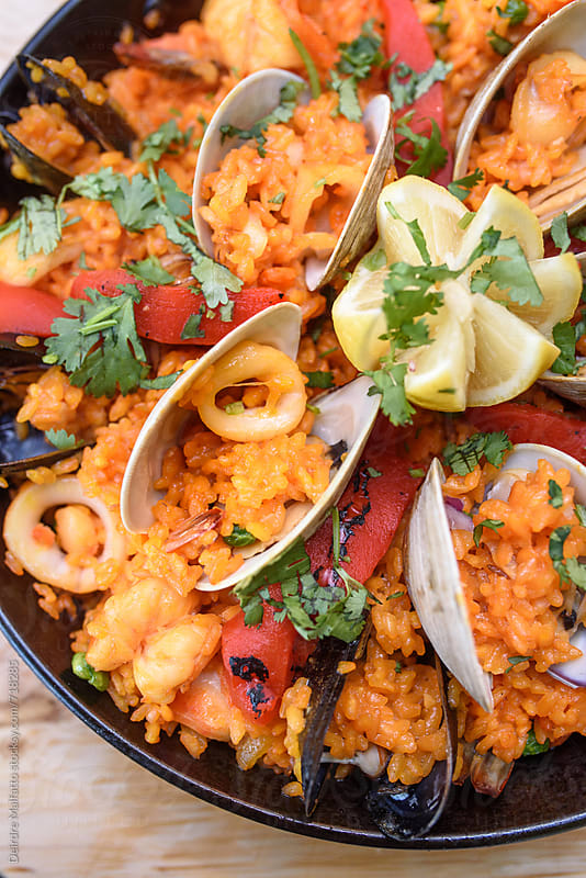 pan of seafood paella from above by Deirdre Malfatto for Stocksy United