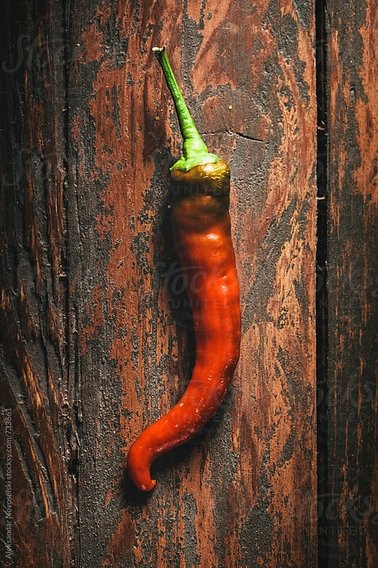 Red hot chili pepper on wooden table by Aleksandar Novoselski for Stocksy United