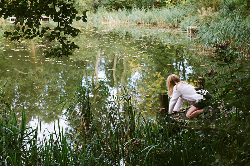 A little girl looking into a pond. by Helen Rushbrook for Stocksy United