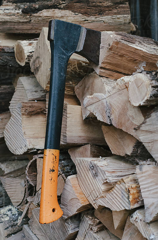 axe stuck in a wood pile by Deirdre Malfatto for Stocksy United