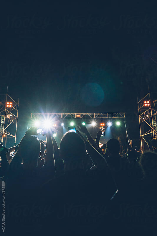 Person taking a picture with your smartphone at a concert in the evening by ACALU Studio for Stocksy United