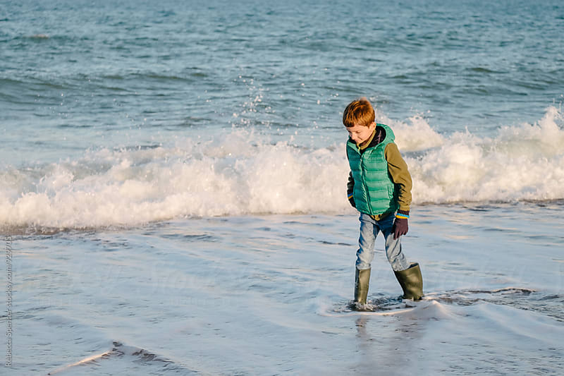 Boy in warm clothes walks along the sea edge with waves behind by Rebecca Spencer for Stocksy United