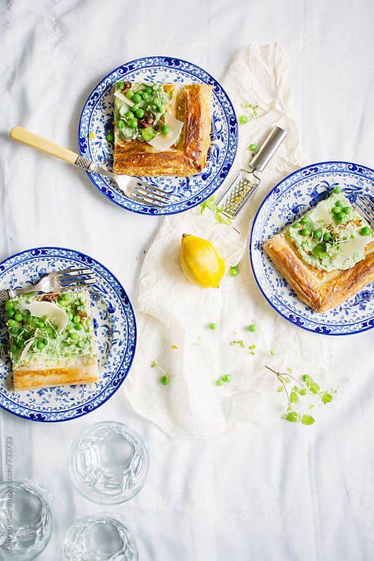 Pea,ricotta and lemon tart with micro herbs and Parmigiano. by Darren Muir for Stocksy United