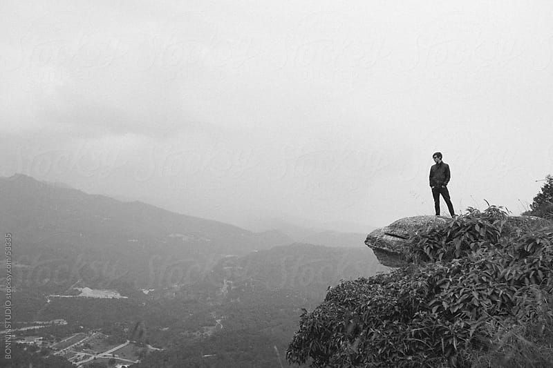 Young modern man observing beautiful landscape on the top of the mountain. by BONNINSTUDIO for Stocksy United
