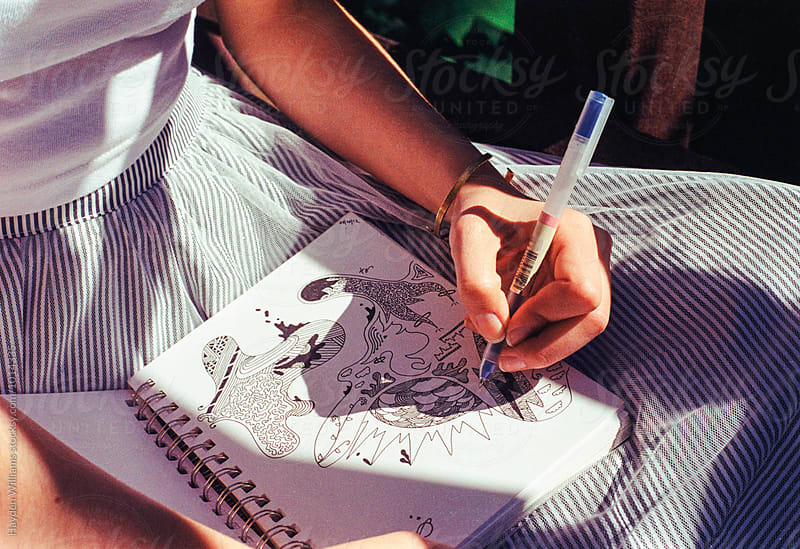Closeup of a woman drawing doodles in her sketch book by Hayden Williams for Stocksy United
