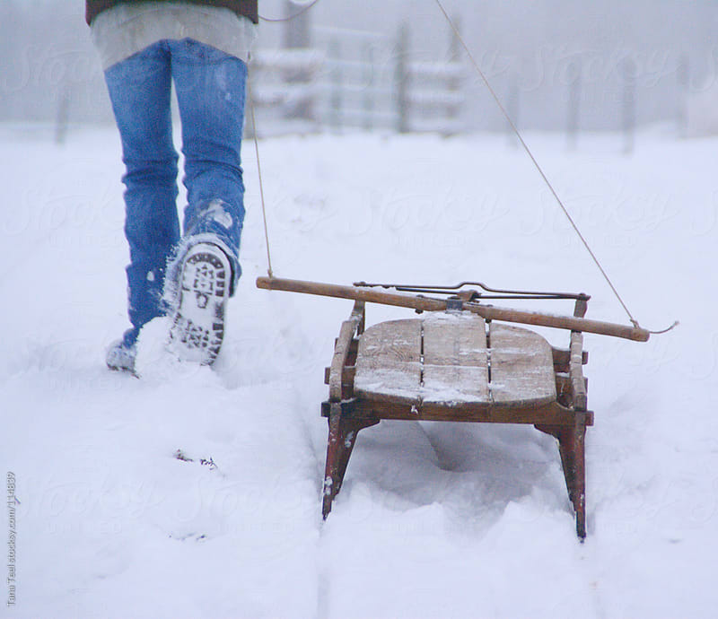 An old wooden sled being pulled up the snowy slope by Tana Teel for Stocksy United