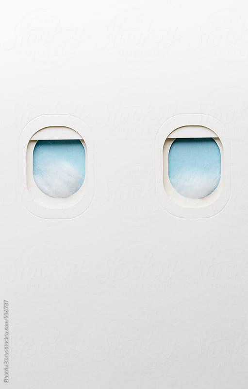 Conceptual travel photo with couple of airplane windows with clouds by Beatrix Boros for Stocksy United