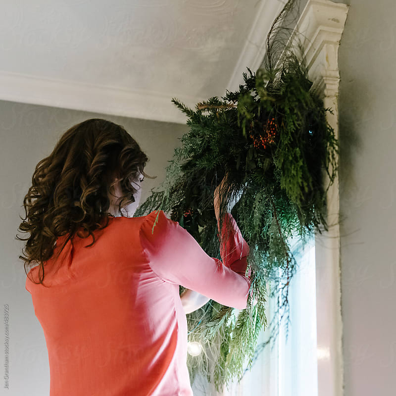 Woman hanging garland over the window by Jen Grantham for Stocksy United