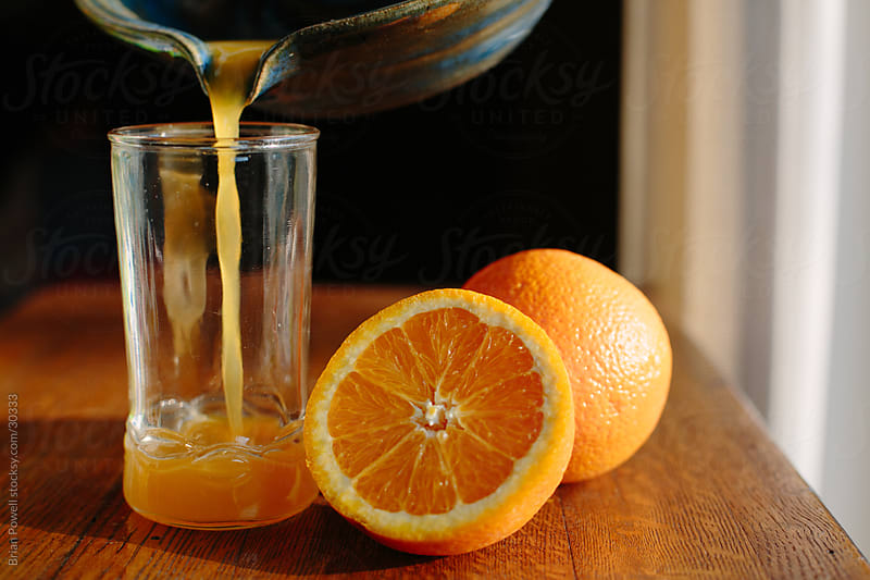 pouring a glass of fresh squeezed orange juice by Brian Powell for Stocksy United