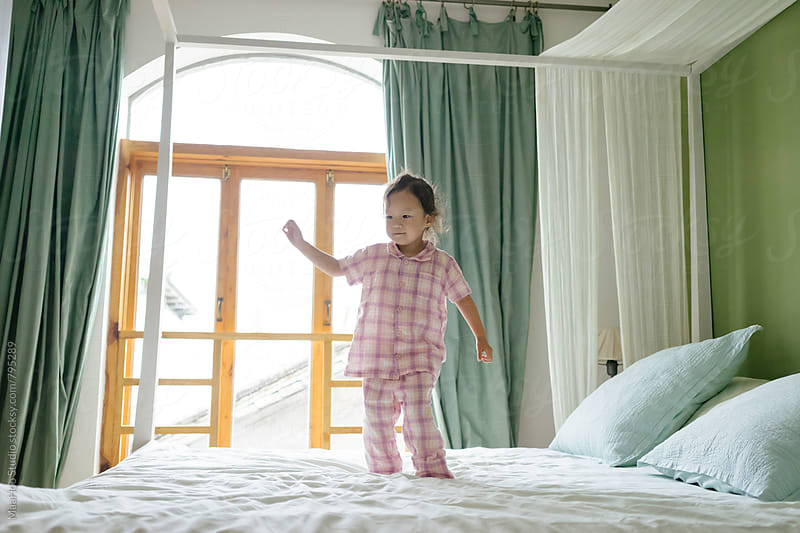 Cute toddler girl playing on bed by Maa Hoo for Stocksy United