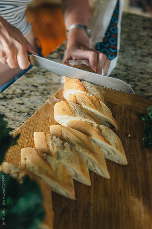 Cutting bread by Jen Grantham for Stocksy United