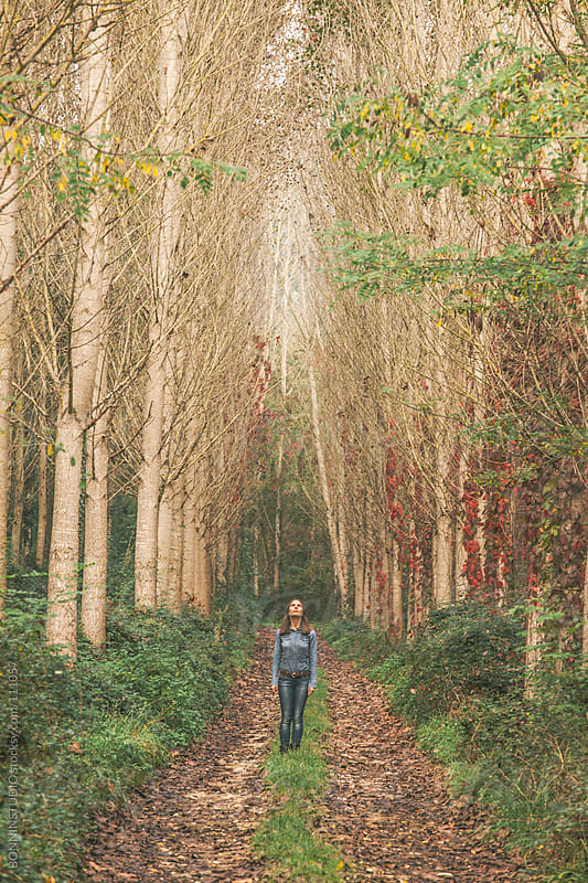 Young woman looking up on a forest road. Autumn landscape.  by BONNINSTUDIO for Stocksy United