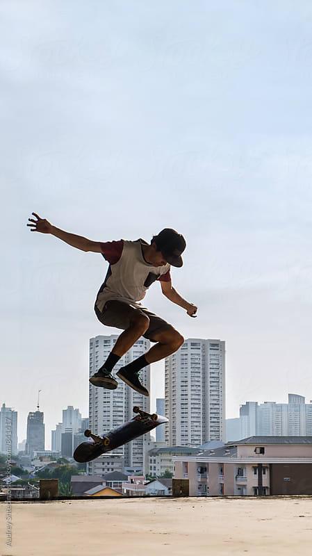 Skateboarder doing tricks on skateboard with cityscape in background. by Marko Milanovic for Stocksy United