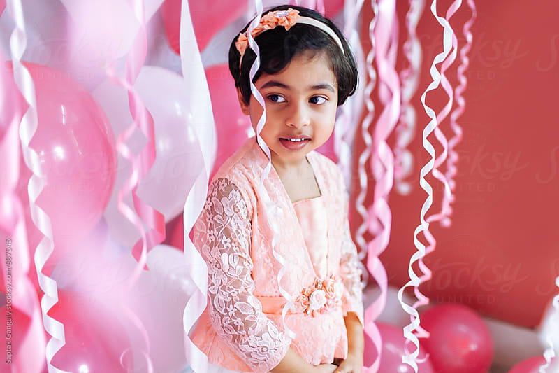 Portrait of cute little girl surrounded by party streamers by Saptak Ganguly for Stocksy United