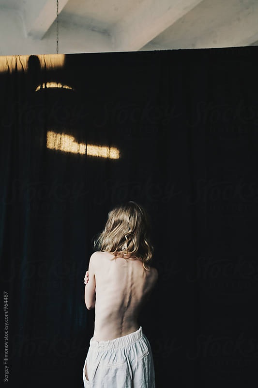 Back view of a young thin blonde woman with long hair by Sergey Filimonov for Stocksy United
