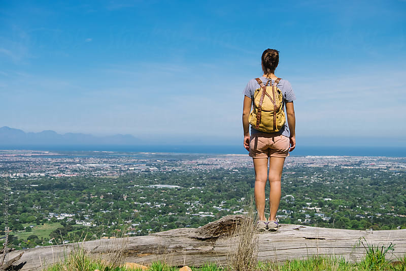 Female hiker overlooking a town by Micky Wiswedel for Stocksy United