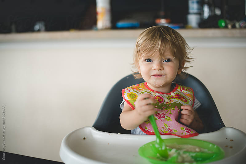 Baby boy with long hair eating in high chair by Courtney Rust for Stocksy United