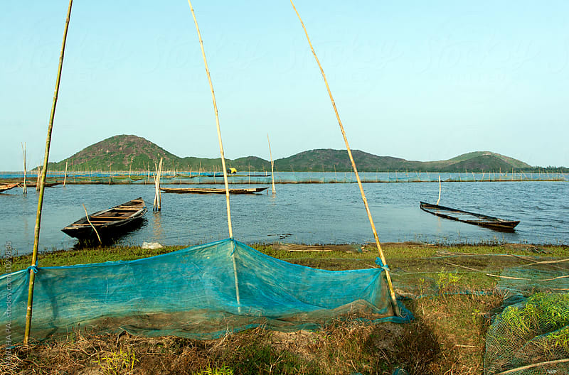 Fishing boat resting on a big lake by PARTHA PAL for Stocksy United
