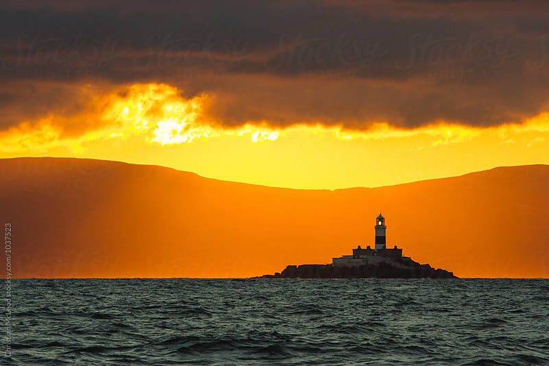 Sun setting upon a lighthouse. by Christian McLeod Photography for Stocksy United