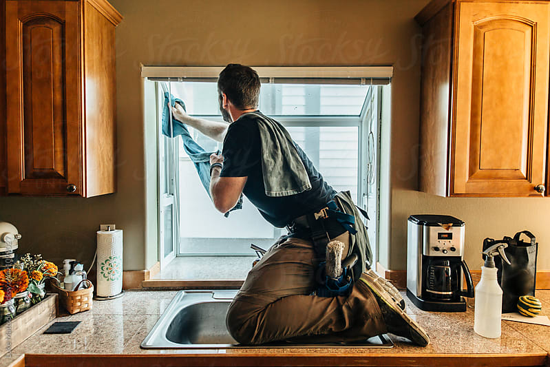 Window Washer On Top Of Kitchen Counter Cleaning Interior Of Win by Luke Mattson for Stocksy United