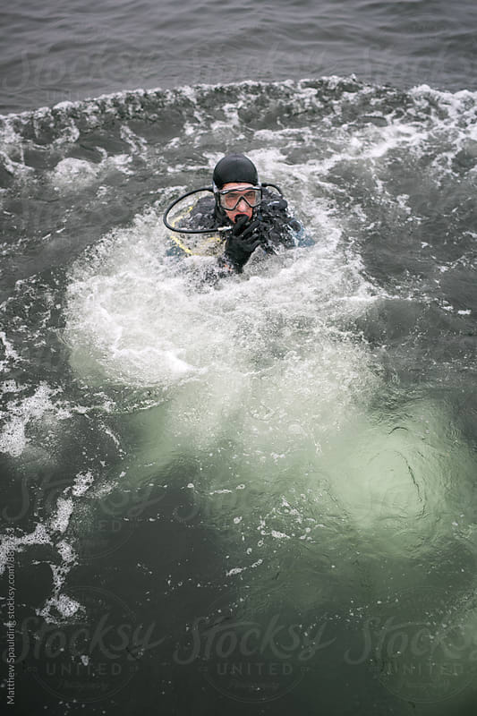 Scuba diver plunging  into cold water  by Matthew Spaulding for Stocksy United