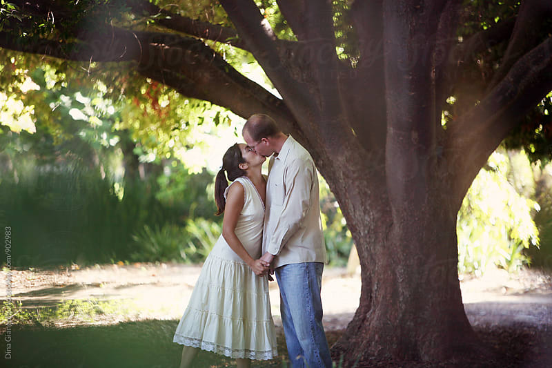 Multi Ethnic Couple Kissing Under A Large Tree by Dina Giangregorio for Stocksy United