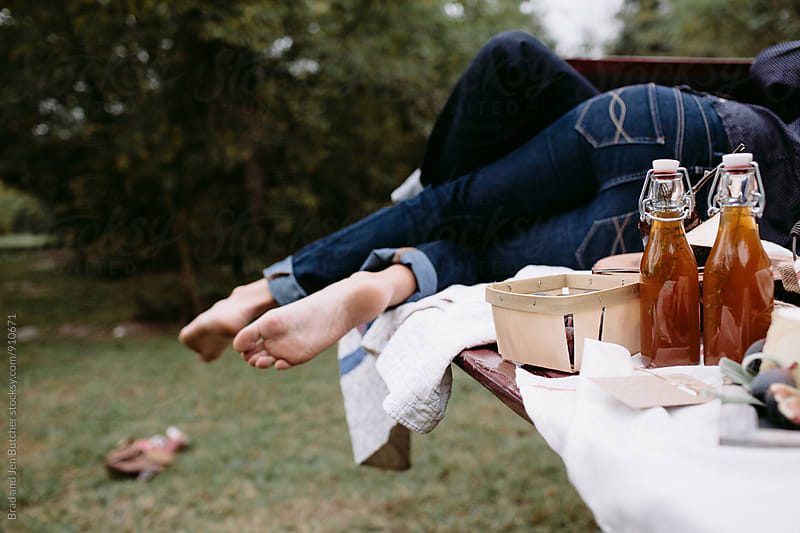 Couple Napping on a Picnic by Brad and Jen Butcher for Stocksy United
