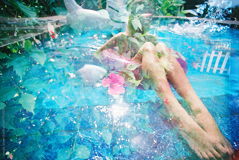 girls legs in pool floaty with floral plants superimposed on top by wendy laurel for Stocksy United