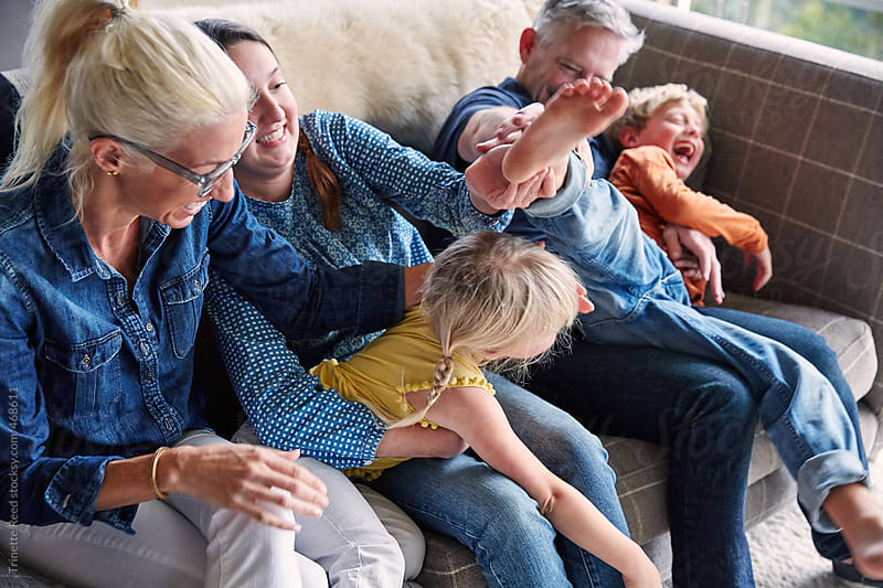 Portrait of family having fun and connecting in living room by Trinette Reed for Stocksy United