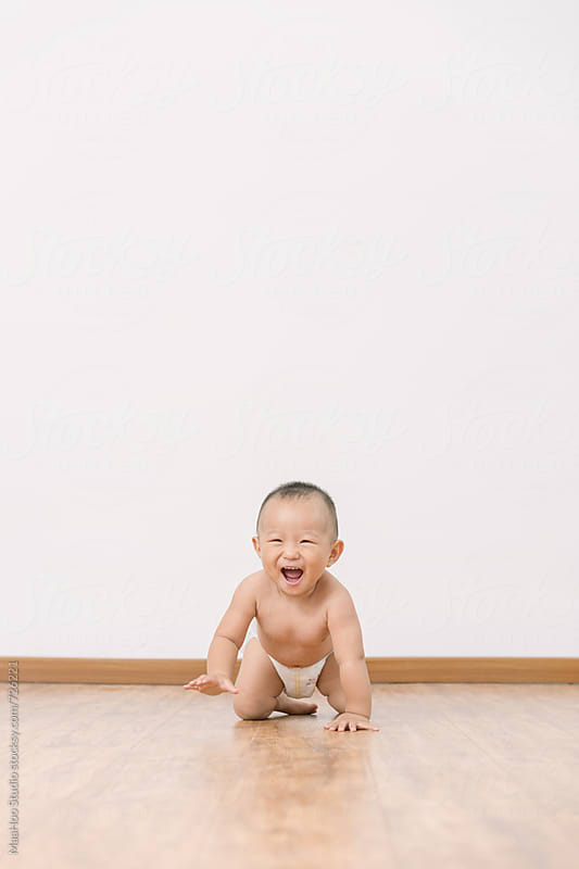 I year old toddler boy crawling on wood floor by Maa Hoo for Stocksy United