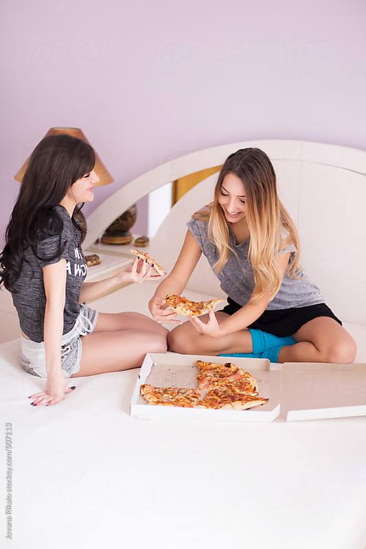 Two young female friends eating pizza at home by Jovana Rikalo for Stocksy United