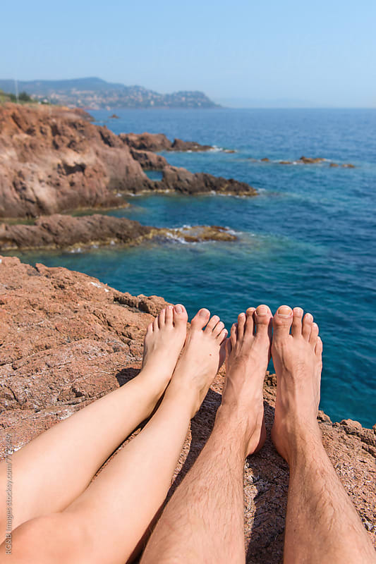 Couple relaxing on a sunny and rocky seashore in the summer by RG&B Images for Stocksy United