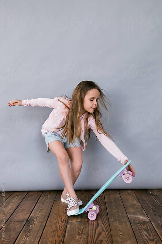 Studio shot of girl skateboarding  by T-REX & Flower for Stocksy United