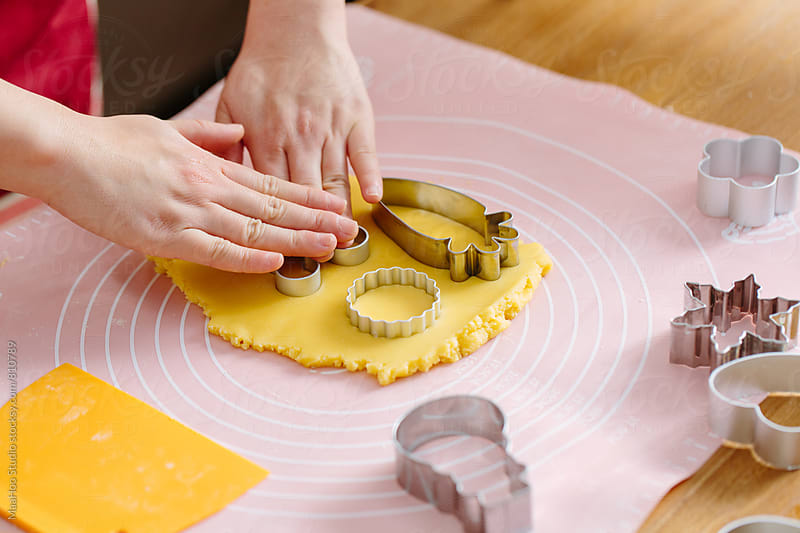 Baker using cookie cutter in dough by Maa Hoo for Stocksy United