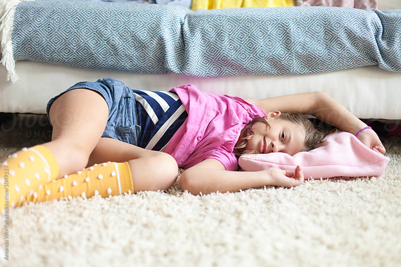 Content preteen girl laying on the floor in the living room, looking at camera by Amanda Worrall for Stocksy United