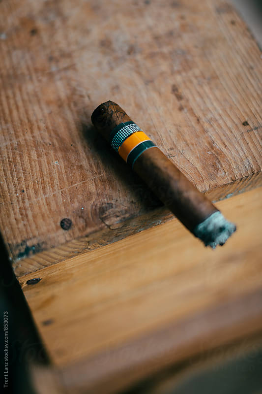 Close-up of half smoked cuban cigar by Trent Lanz for Stocksy United