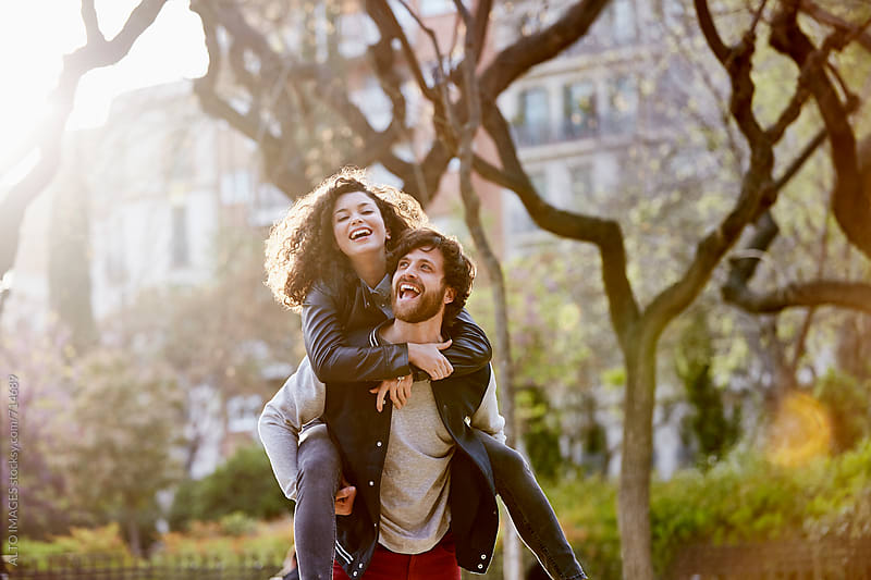 Couple Enjoying Piggyback Ride In City by ALTO IMAGES for Stocksy United