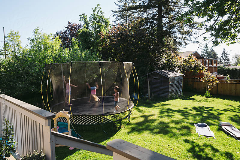 Three young kids jumping on the trampoline in backyard by Rob and Julia Campbell for Stocksy United