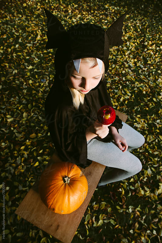 A girl in a bat costume, a pumpkin and a toffee apple. by Helen Rushbrook for Stocksy United